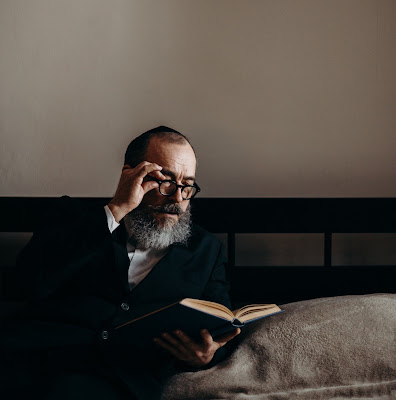 Jewish man reading a book on Nittel nacht