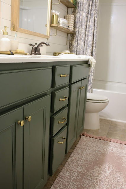 A bathroom vanity painted sherwin williams rosemary with brass hardware