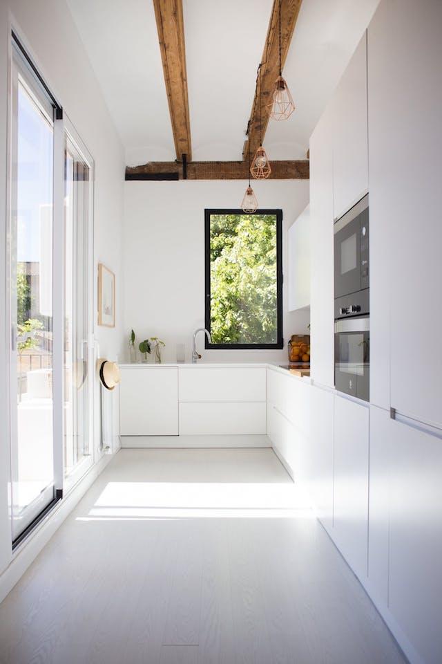 cocina blanca, con electrodomésticos integrados y vigas de madera. Encimera de Corian