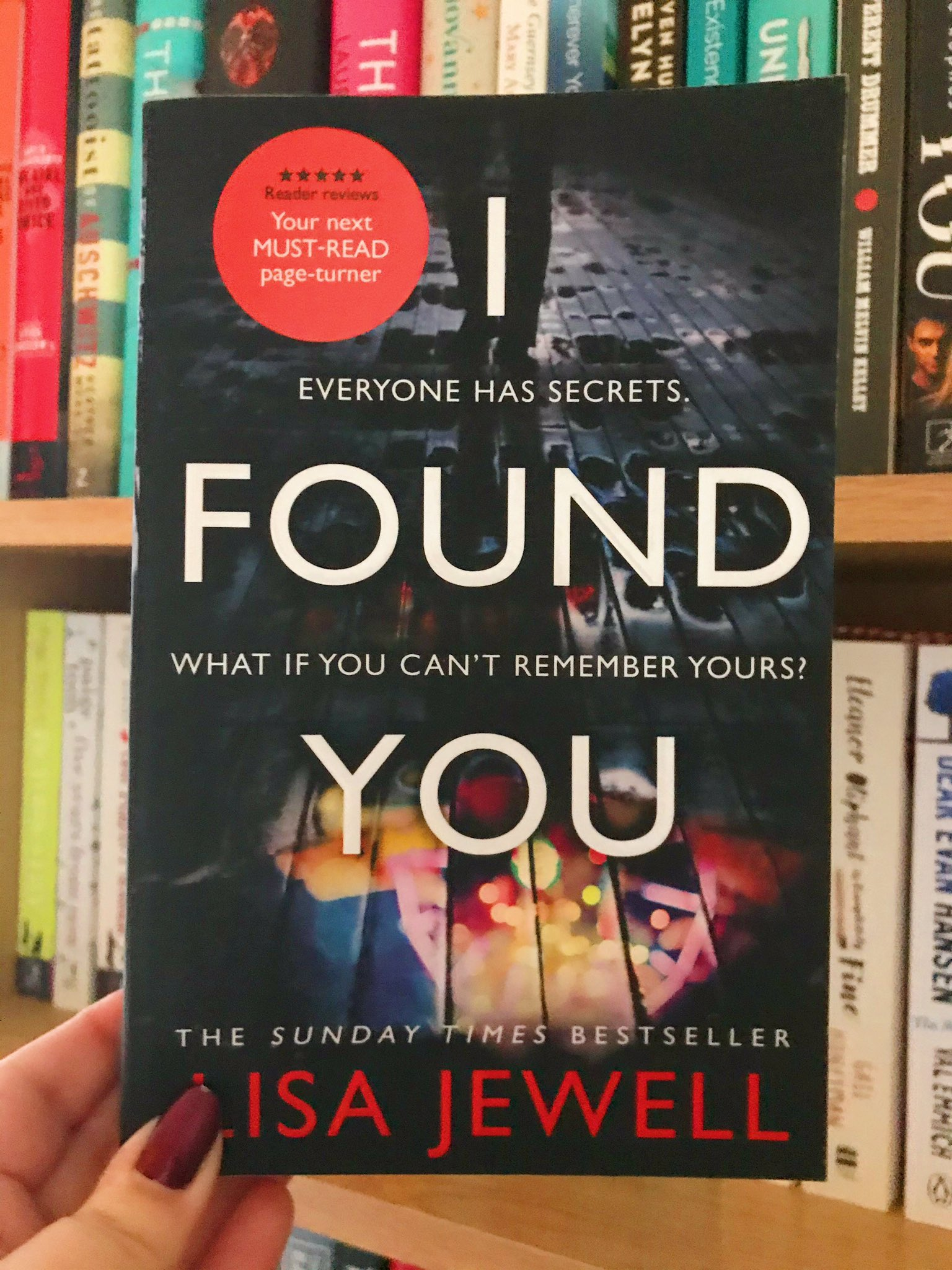 I Found You by Lisa Jewell book held up in front of bookshelf