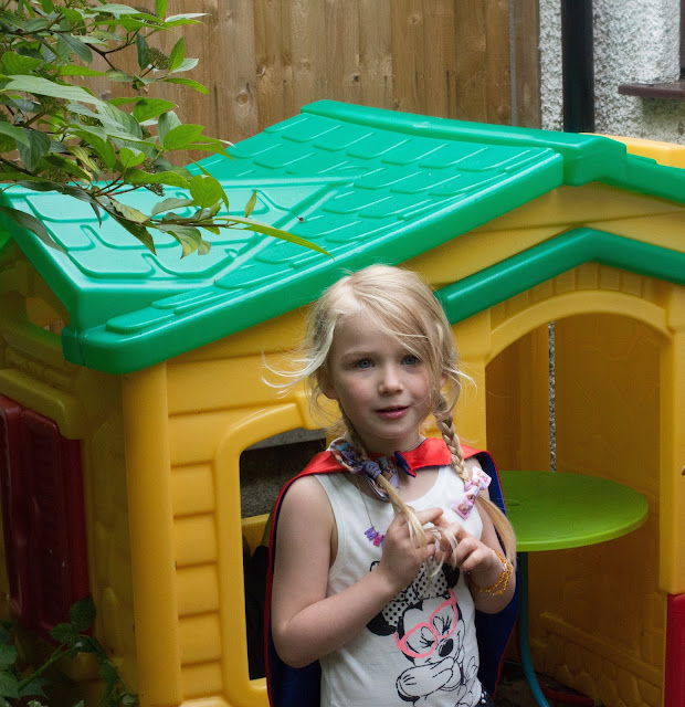 A 4 year old girl in a Wonderwoman cape and minnie mouse dress standing in front of a yellow and green Little Tikes play house