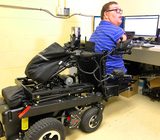 Kyle Romano is shown utilizing the functionality of his wheelchair's seating system. The seat is lowered almost to the floor, while he leans in to type on his keyboard