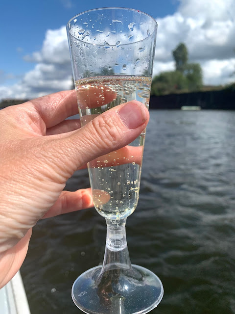 hand holding glass of prosecco on boat with view of river