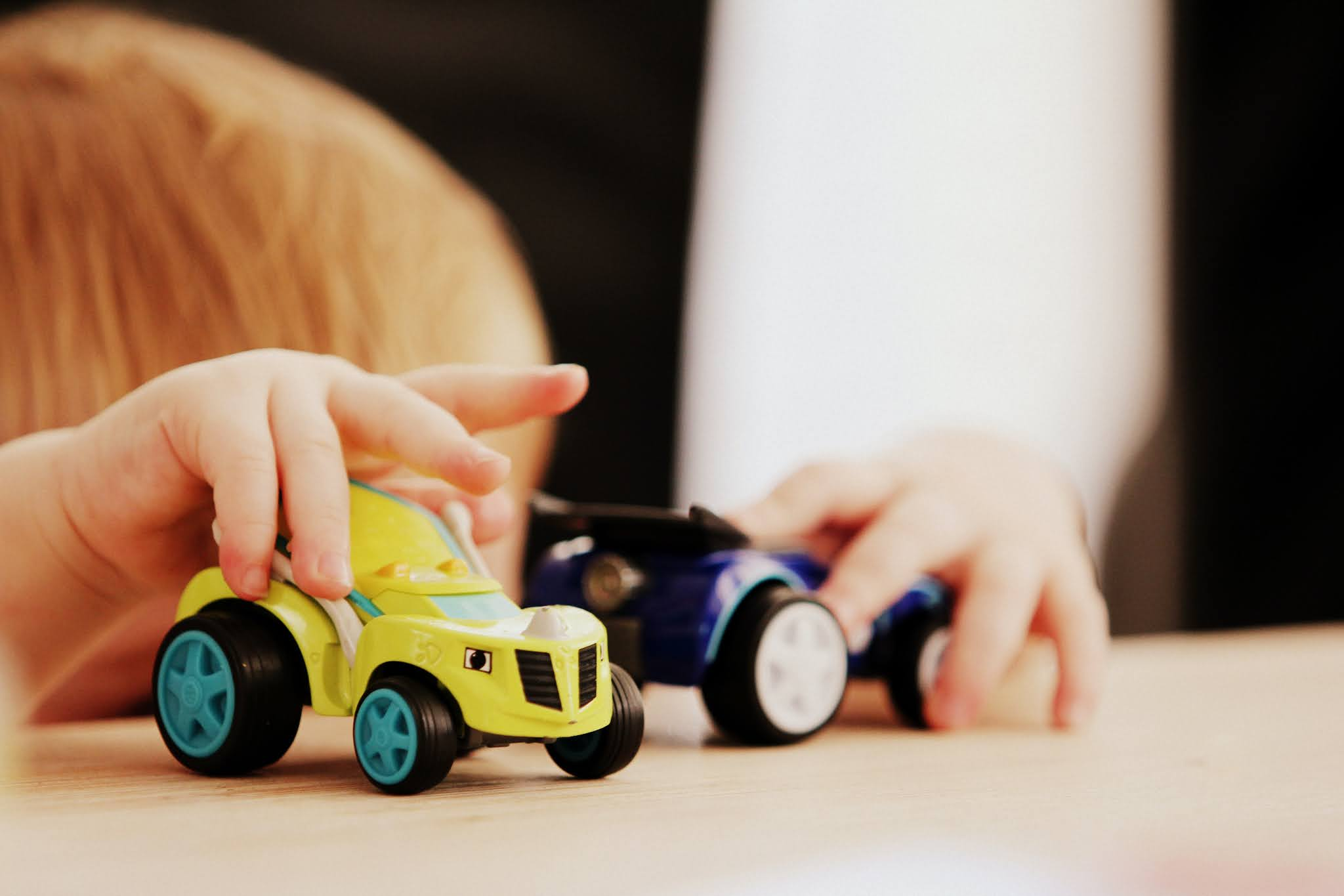 Small child playing with 2 toy cars at head height on a brown table