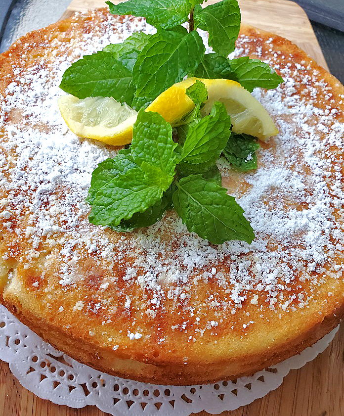 this is a homemade lemon cake with powdered sugar and mint on top