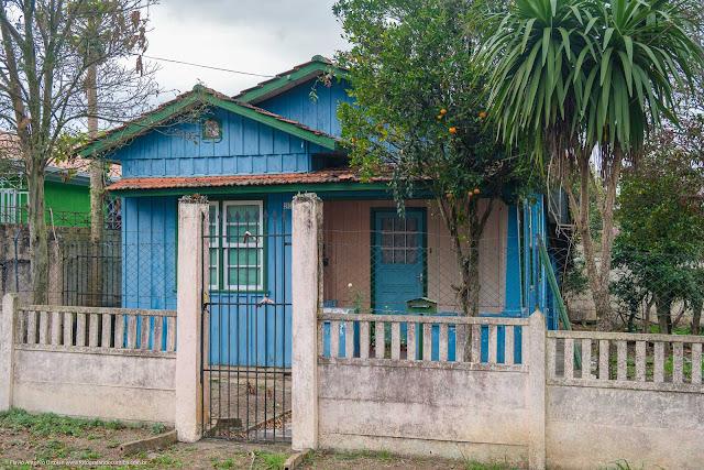 Casa de madeira pintada de azul com capelinha na fachada