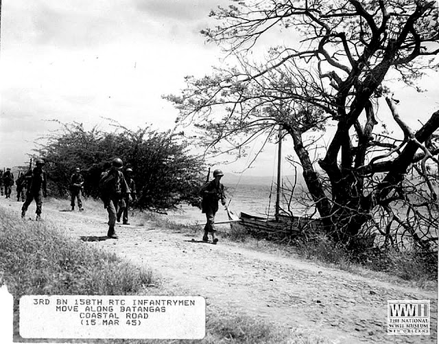 Image credit:  The Digital Collections of the National WWII Museum.  Members of the 158th  RCT walking along a coastal road.  Photo sent in by Jigger Gilera, MD.