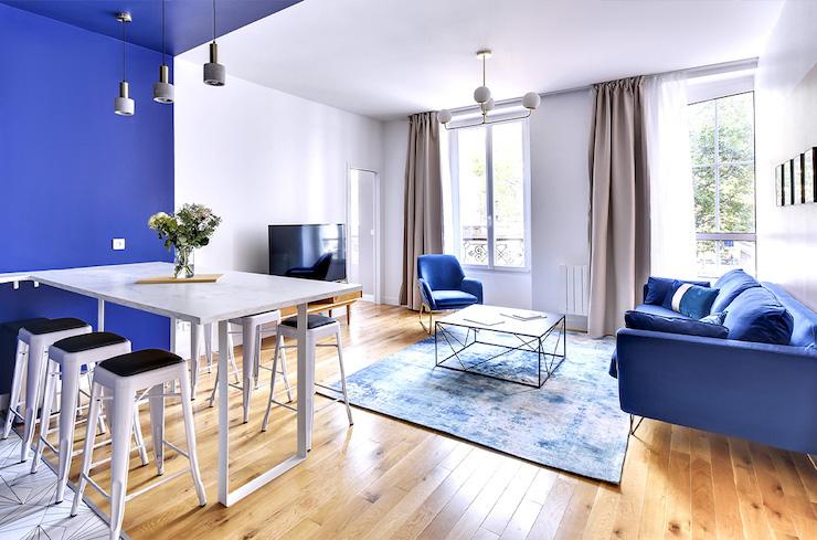 Salón clásico con cocina abierta y mesa a medida