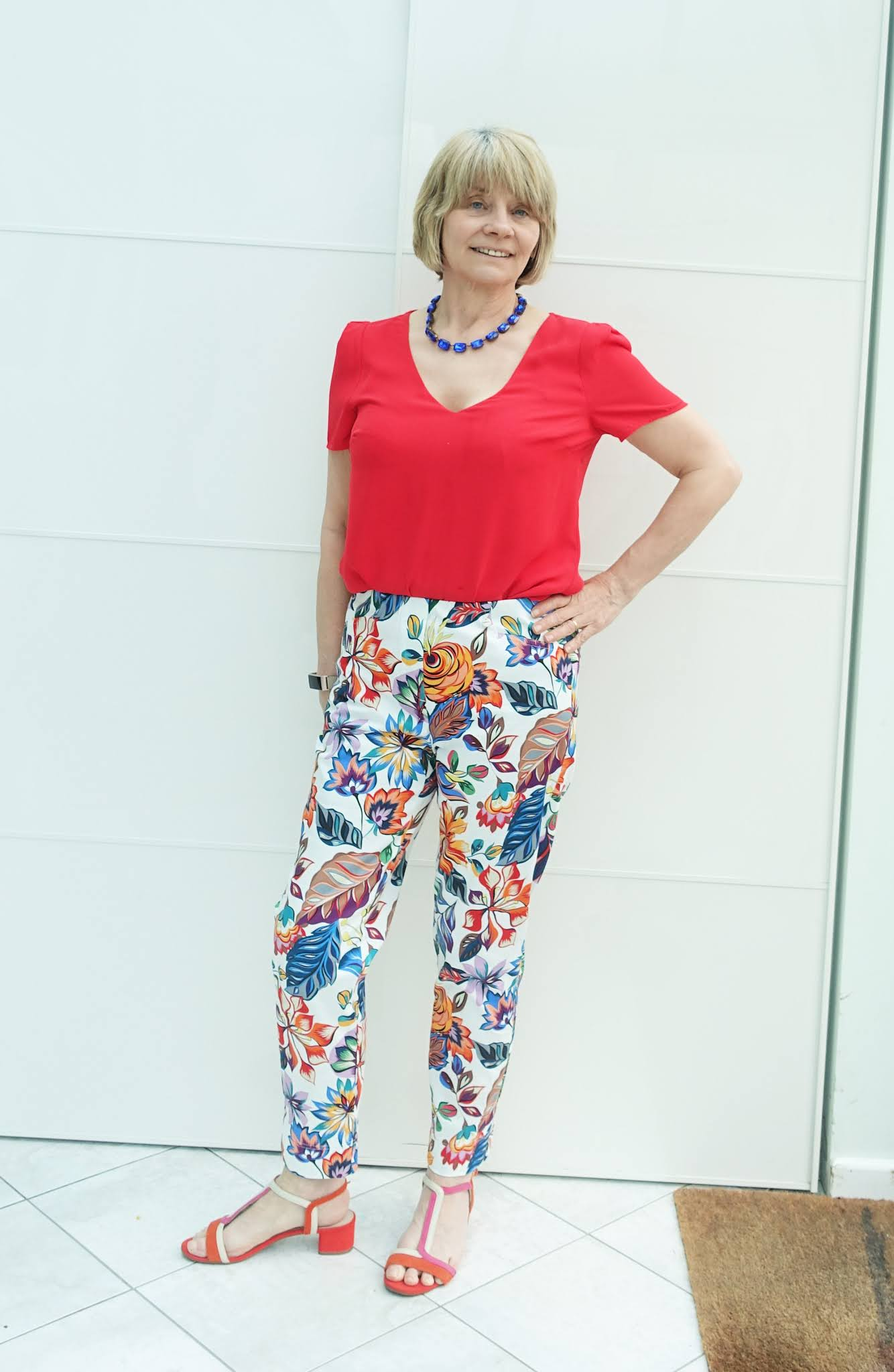 Trousers with a botanical print paired with a red top and sandals by style blogger Is This Mutton
