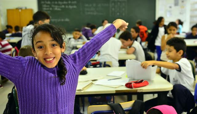 Menina com colegas alunos em atividade em sala de aula