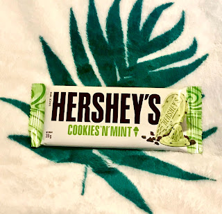 A rectangular white bar in white packaging with Hersheys in black big font with cookies 'n' mint in green font on a bright background