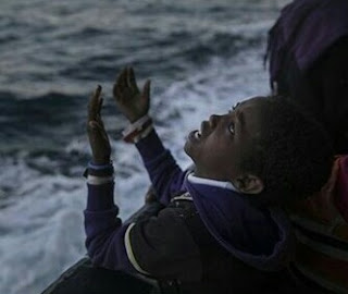 Photo of an African child crying while celebrating his arrival to Europe after being rescued from the Mediterranean Sea