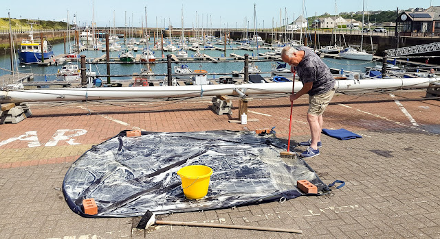 Photo of scrubbing the flybridge cover in the sunshine