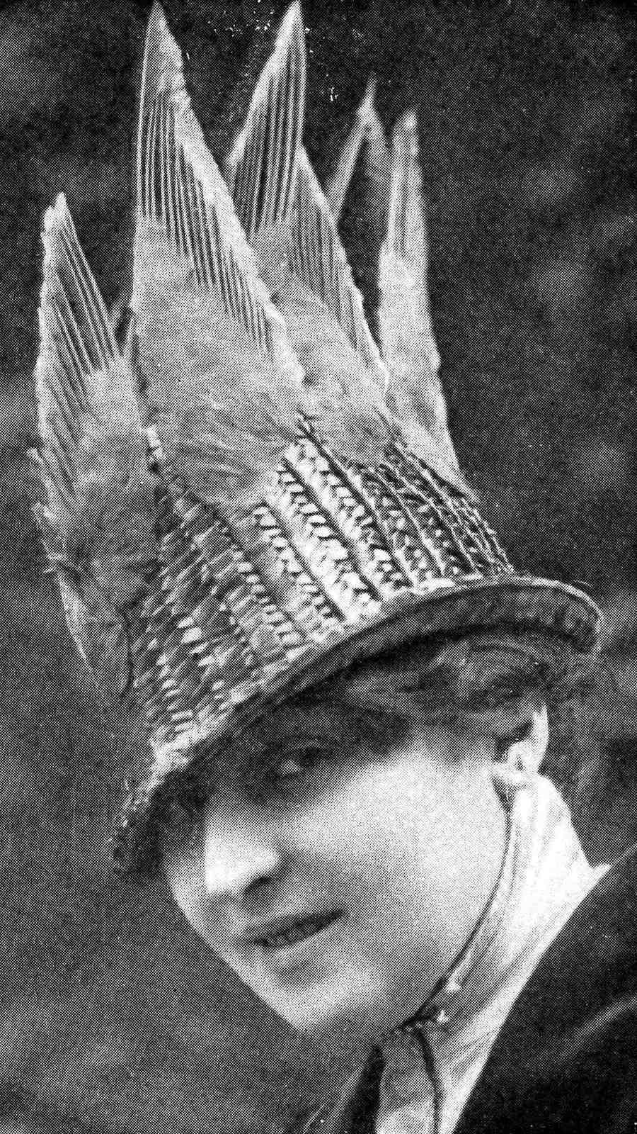 a high fashion photograph in 1915 France, a woman's hat with bird feathers