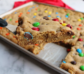 first piece salted caramel M&M blondies lifted out of pan on spatula showing chewy fudgy center