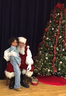 Santa kneeling next to a Christmas tree with a young child next to him