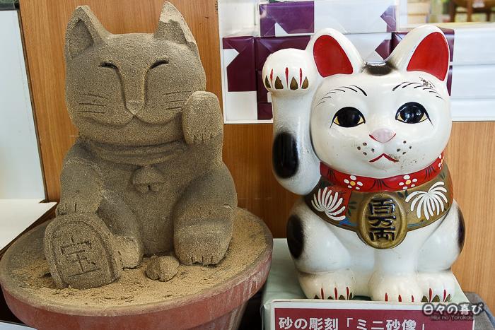 sculpture de sable de maneki neko à côté de son modèle