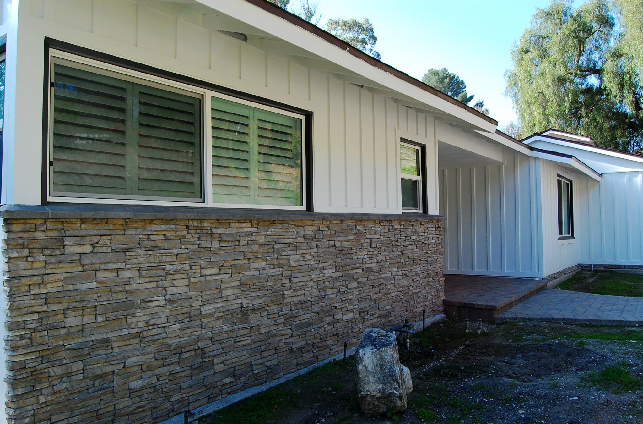 mid-century ranch house exterior home remodel and improvements pavers stone black craftsman entry door board and batten black and white