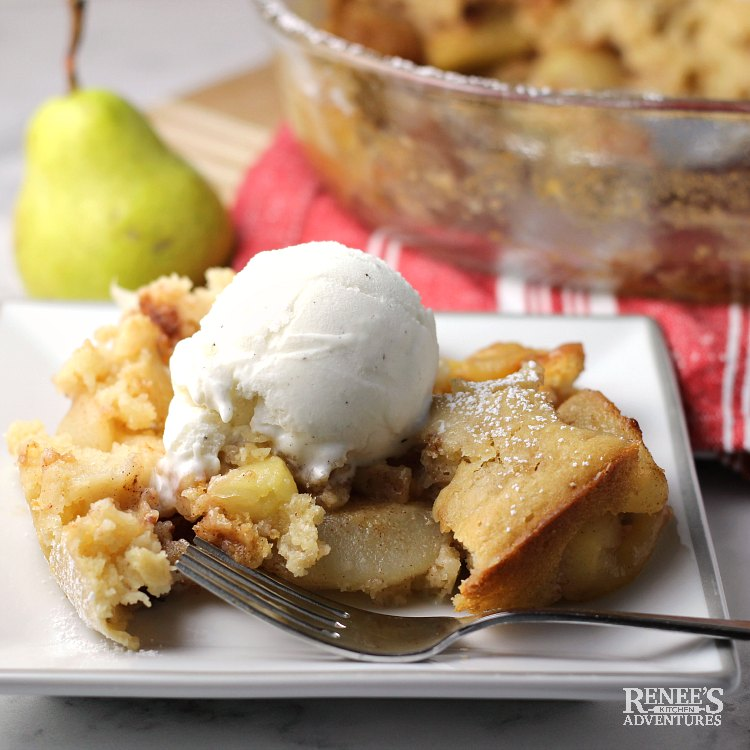 Warm Pear Cobbler by Renee's Kitchen Adventures on a white plate with a scoop of vanilla ice cream and a fork with a fresh pear in the background on red and white linens