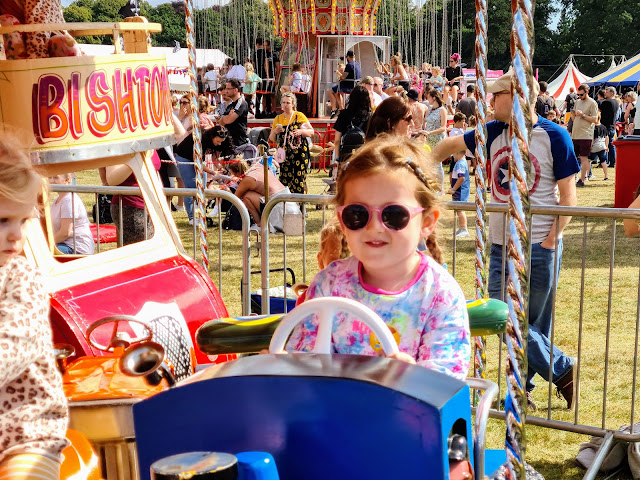 Image of a young girl with plaited hair, pink sunglasses and a tie dye top riding in a plane on a vehicle themed children's ride. In the background there are circus tents and a carousel ride.