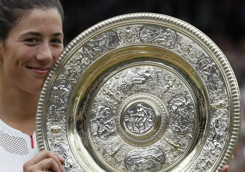 Spain's Garbine Muguruza holds the trophy after defeating Venus Williams of the United States in the Women's Singles final match on day twelve at the Wimbledon Tennis Championships in London Saturday, July 15, 2017. (AP Photo/
