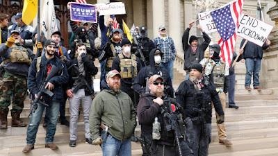Manifestantes fazem protesto com armas e símbolo nazista contra a quarentena em Michigan