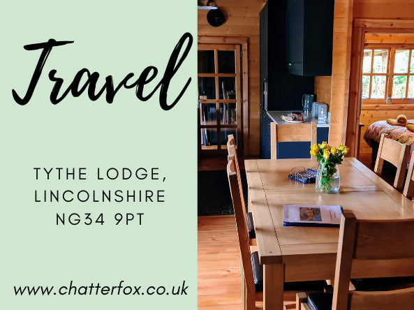 Title image for blog post with text that reads 'travel and days out Tythe Lodge Lincolnshire NG34 9PT www.chatterfox.co.uk alongside an image of the inside of the lodge featuring a blue kitchen, a wooden dining table that seats six and a view into the double bedroom with en suite shower room.