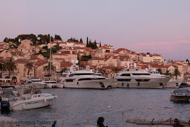 Pink sunset, boats, and skyline in Hvar, Croatia
