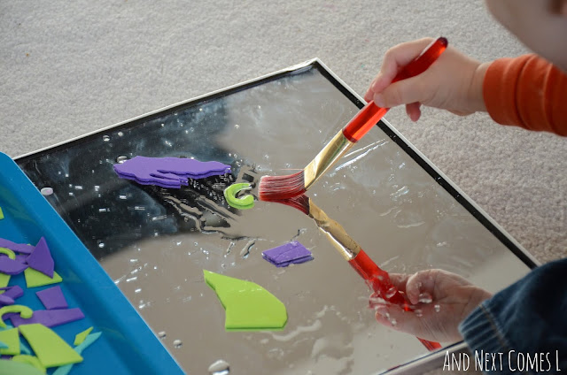 Toddler painting with water on a mirror