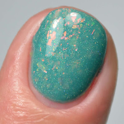 teal nail polish with flakies close up swatch