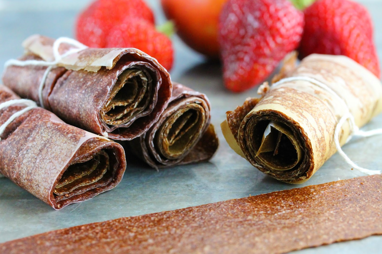 A stack of No Simmer Strawberry-Nectarine Fruit Roll Ups rolled in parchment paper and tied with a string