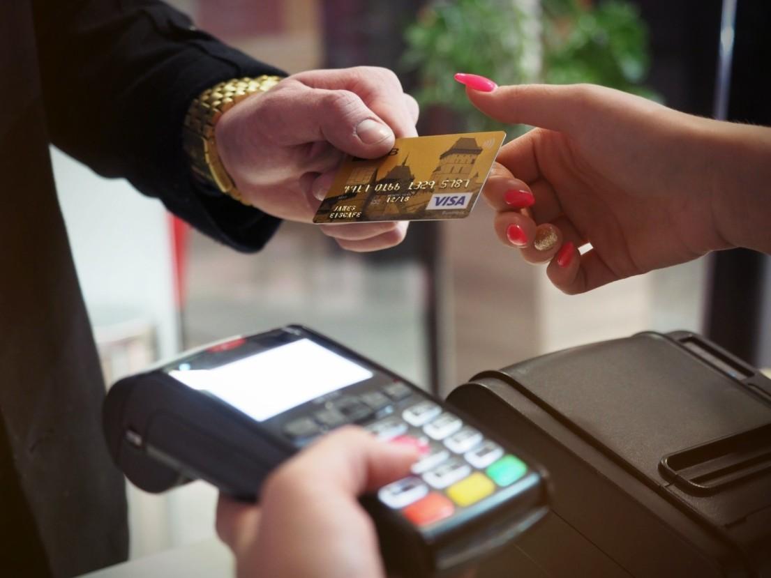 Someone handling a Visa card to Merchant
