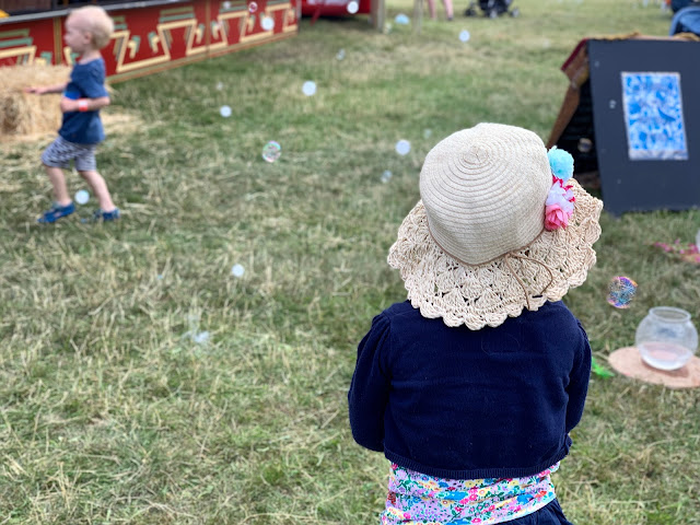 A toddler in a straw sun hat watching bubbles at the 3 foot people festival