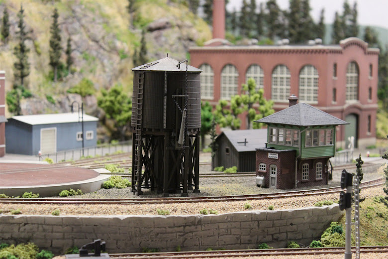 Completed Atlas Water Tower and Signal Tower kits installed in a rail yard in a model railroad industrial scene