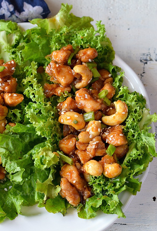 a white plate with cashew chicken lettuce wraps
