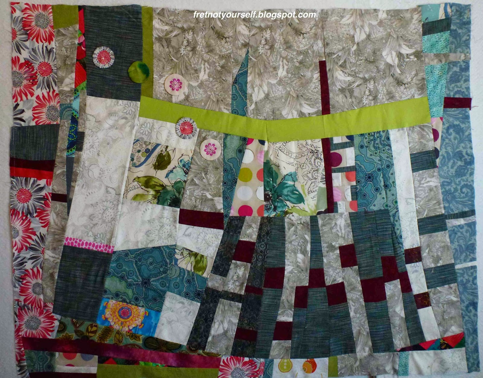 Scraps of medium blue, red, white, grey and green added to the sides of an improvisational quilt.