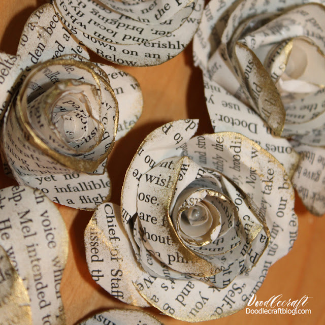 roll and hot glue scalloped cut book pages into rolled rosettes and cover the edges with gold ink.