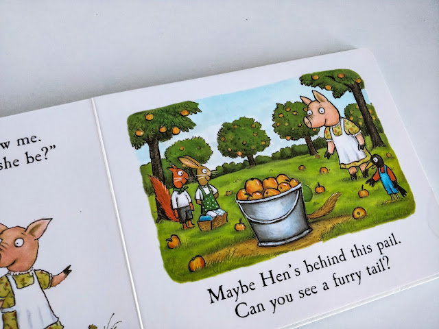 "An up close image of a book open on a page with the illustration of a animals in an orchard full of fallen apples. to the left stands an orange squirrel wearing brown shorts, a white half length sleeve top and a green necktie, beside a brown rabbit wearing a green pinafore with white polkadots on and a white t-shirt underneath. A big pail of red and yellow apples sit in the middle, to the right stands a pig in a yellow dres with red flowers all over and a white apron over the top. Just in front of the pig stands a crow wearing a red shirt with blue overalls. Below the image reads "" Maybe Hen's behind this pail. Can you see a furry tail?"""