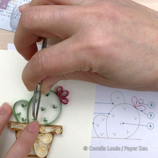 hand showing placement of on-edge folded paper strip on quilled cactus card