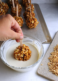 dipping caramel apple popcorn balls in white chocolate with tray of chopped peanuts nearby
