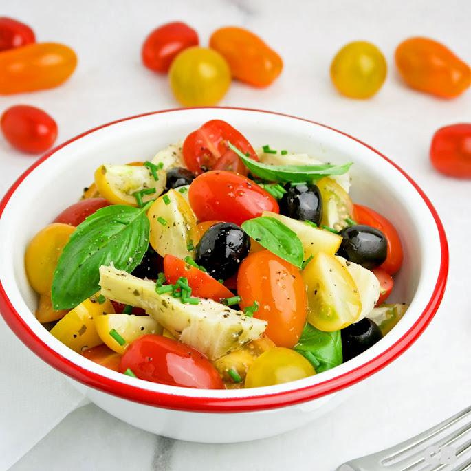 Salade van allerlei kleuren cherrytomaatjes, artisjokken en olijven