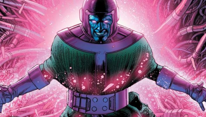 Imagem: o Kang dos quadrinhos, um homem com um elmo arroxeado e rosto azulado, como que metálico, olhos brilhantes e roupas verdes, além de luvas roxas, emitindo uma energia rosa.