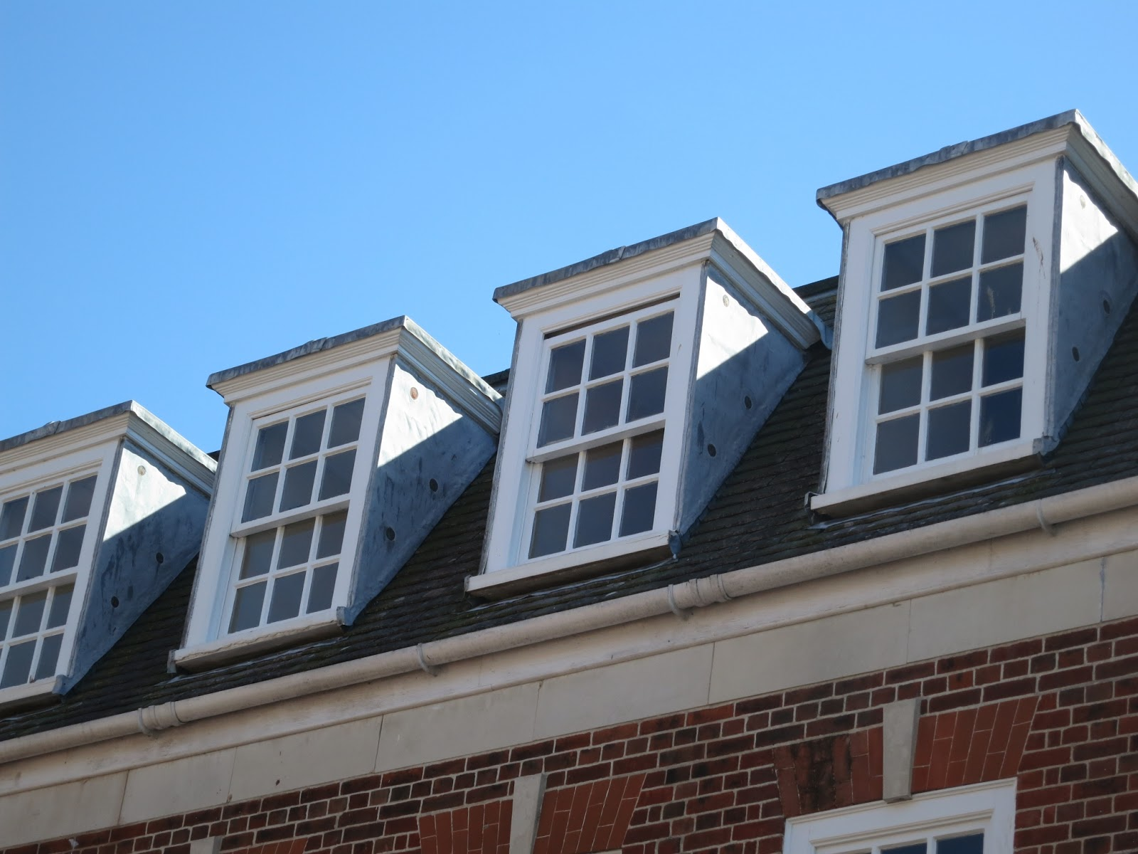 Four sash windows in the attic of a brick building.