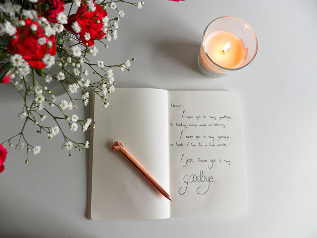 A book sits open on a table, inside a poem is written called I never got to say goodbye, a rose gold pen with an elephant on top sits on the opposite blank page. to the right above the book is a cream coloured lit candle in a glass holder. To the left is a bouquet of red chrysanthemum and baby's breath that sit closer to the camera.
