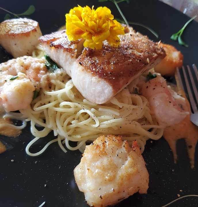 this is a sea bass over pasta with shrimp and scallops