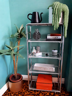 Corner of a one-twelfth scale modern miniature art-deco inspired room, with a chrome and glass bookshelf containing various ornaments, books and a hanging planet.
