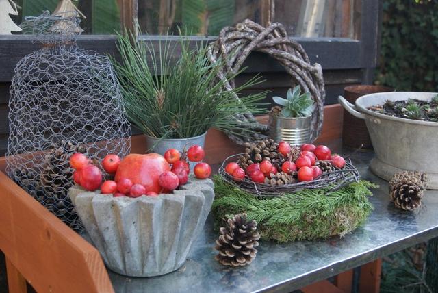 Pflanztisch dekoriert mit Kranz, Zapfen und Zieräpfeln