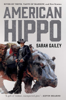 A person in a dark suit and black knee-high boots with a wide-brimmed hat leans casually against the side of a large hippo with a saddle and saddlebags.