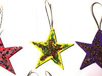 Estrellas brillantes realizadas por niños con papel y brillantina como adornos navideños.