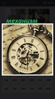 на листе бумаги с записями лежит механизм часы с римскими цифрами